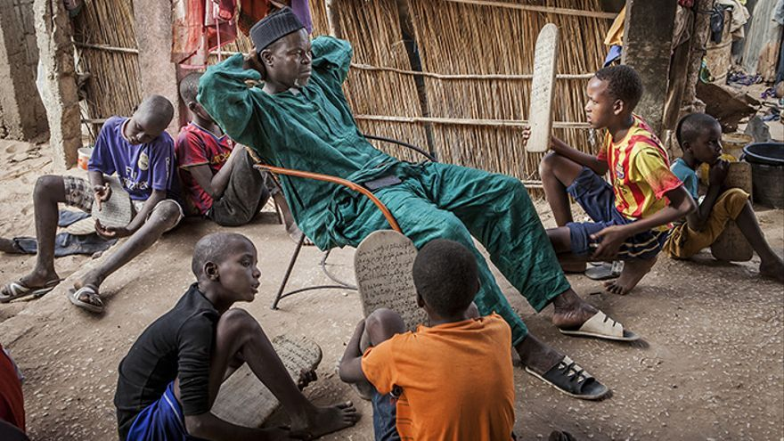 Un alumno enseña su tablilla, escrita con versos del Corán, a su marabout ( D. Moudou). Daara en M'bour, Senegal.   Lucas Vallecillos.