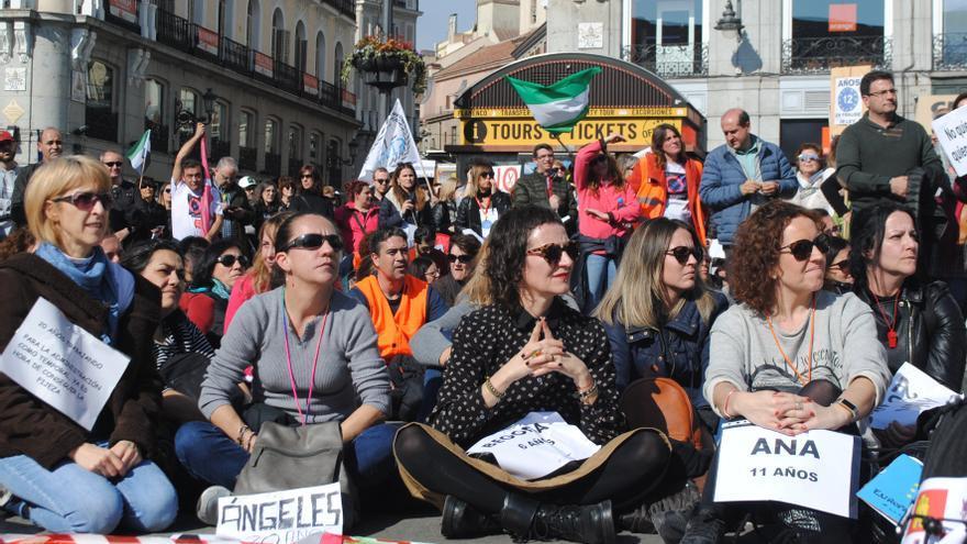Un grupo de manifestantes escucha las reivindicaciones del colectivo en la Puerta del Sol.