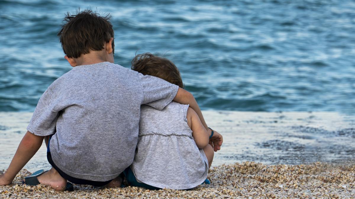 Dos hermanos observan el mar.