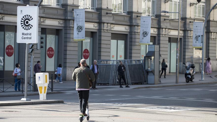 Un hombre en patinete eléctrico por las calles de Madrid al lado de un cartel de Madrid Central