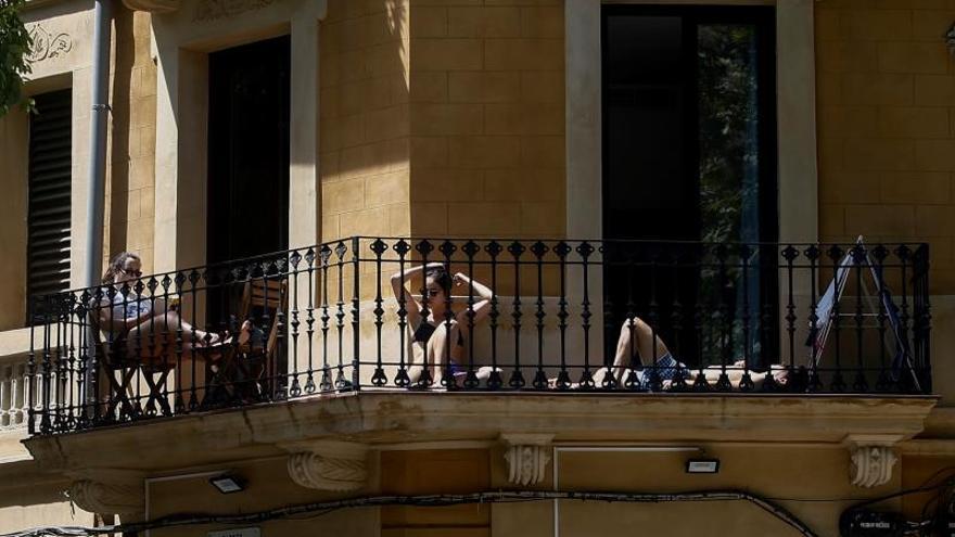 Tres jóvenes toman el sol en el balcón en un piso del barrio del Eixample de Barcelona durante el estado de alarma.