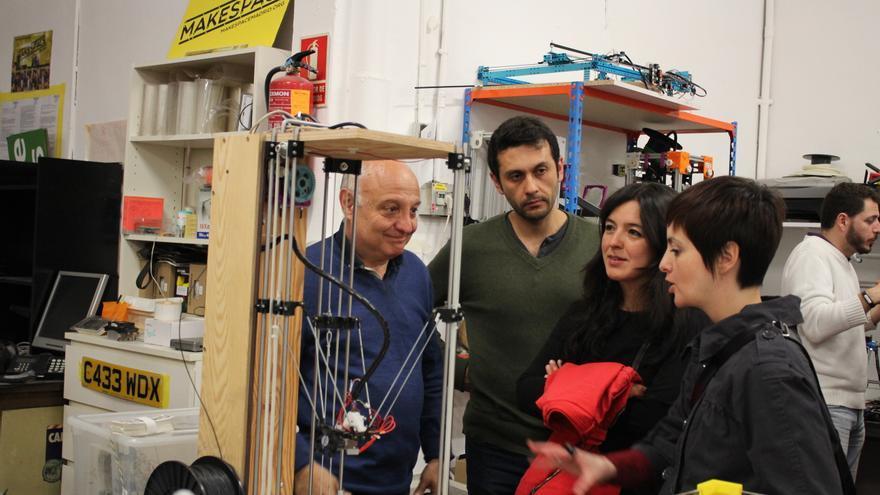 Javier Martínez (a la izquierda) comenta el funcionamiento de la impresora 3D delta de este espacio