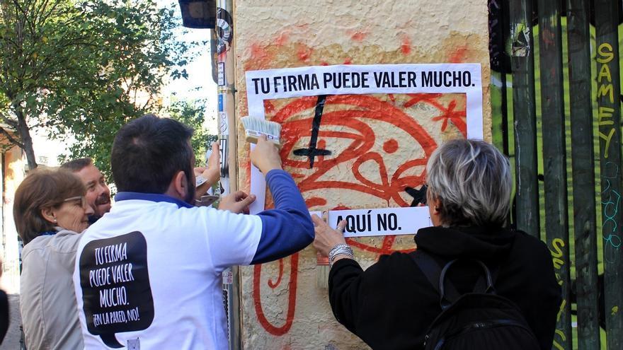 Vecinos colocan los carteles de la campaña 'Tu firma puede valer mucho'   SOMOS MALASAÑA