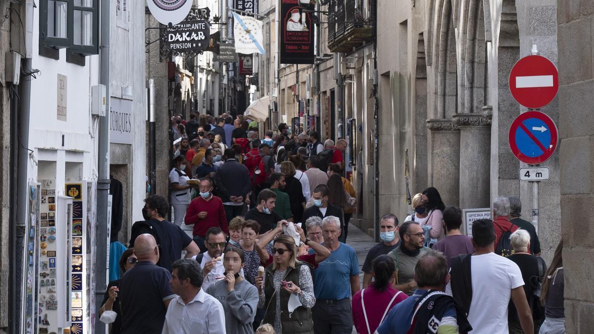 Varias personas caminan por la calle del Franco el mismo día en el que se amplían los aforos al 90% en interiores, en Santiago de Compostela, A Coruña, Galicia
