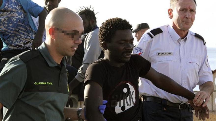 Un Guardia Civil y un policía marroquí conducen a una persona a su llegada a las costas españolas (EFE)