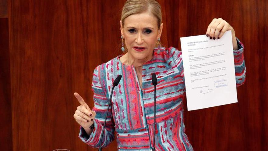 Cristina Cifuentes documentos sobre su máster durante una sesión de la Asamblea de Madrid.