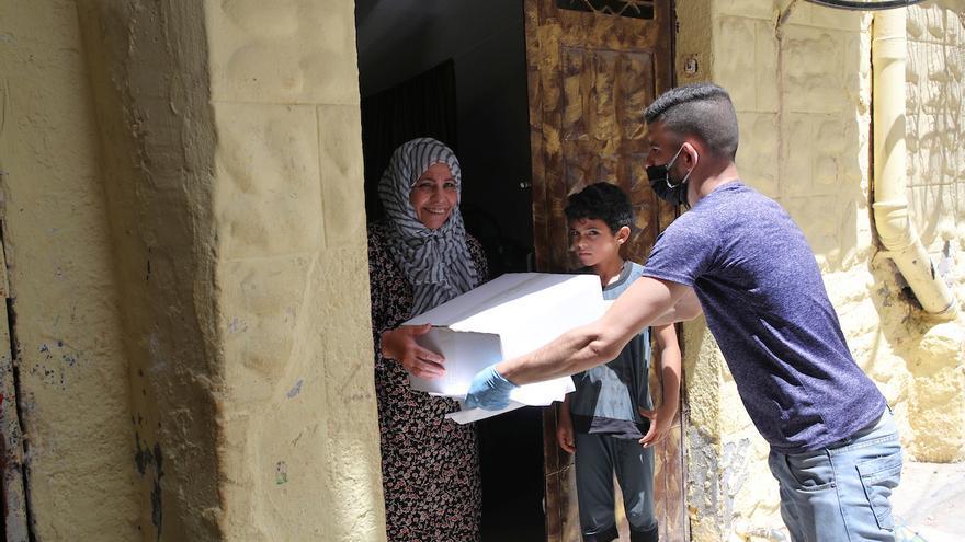Una mujer refugiada recibe una cesta de alimentos de UNRWA en casa