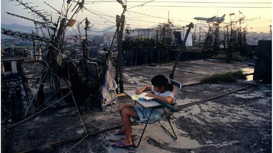 Una niña hace los deberes en una terraza rodeada de antenas de televisión