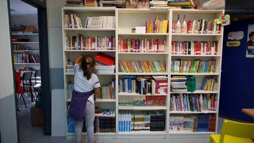 Una niña busca libros en la biblioteca de su colegio.
