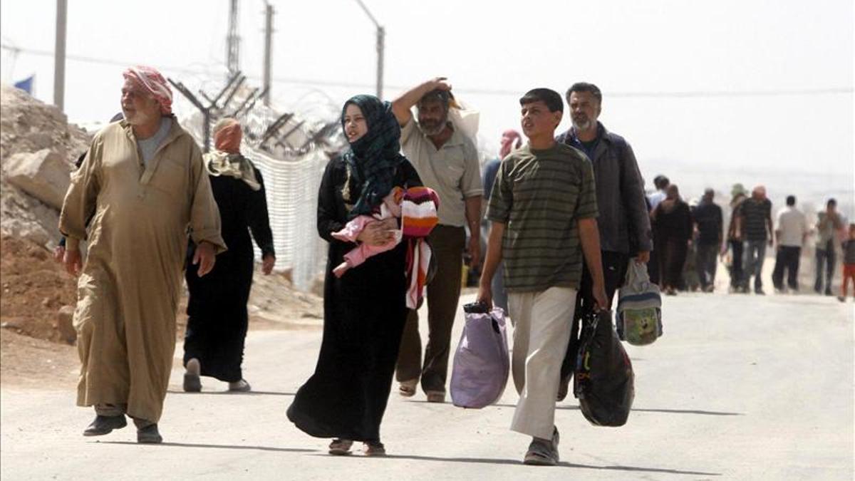 Refugiados sirios caminan con sus pertenencias, en el nuevo campo de refugiados sirios de Zaatari, cerca de la ciudad de Mafraq, Jordani.