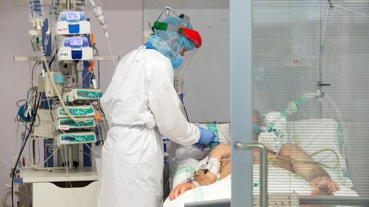 Un sanitario atiende a un paciente con coronavirus.