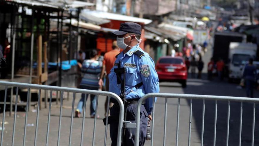 Un policía vigila en un reten colocado en un mercado este lunes, en la ciudad de Comayagüela (Honduras). Decenas de vendedores fueron desalojados este lunes en Honduras por desobedecer el toque de queda absoluto impuesto para enfrentar el coronavirus en el país, donde el fin de semana fueron detenidas 219 personas y 14 inmigrantes retornados se escaparon de un centro donde fueron puestos en cuarentena. El Gobierno estableció el toque de queda absoluto desde el pasado lunes para tratar de frenar la propagación del COVID-19, que hasta ayer afectaba a 27 personas en el país, que está en emergencia sanitaria.
