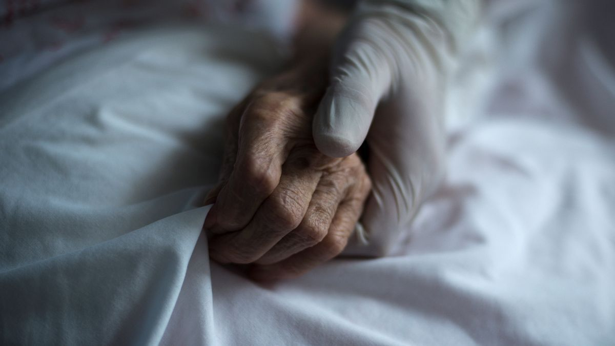 Una trabajadora de una residencia sujeta la mano de una residente. EFE/Brais Lorenzo/Archivo