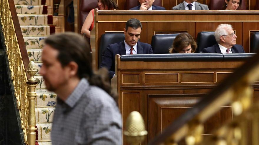 Sánchez cabizbajo mientras Iglesias interviene en el debate de investidura.