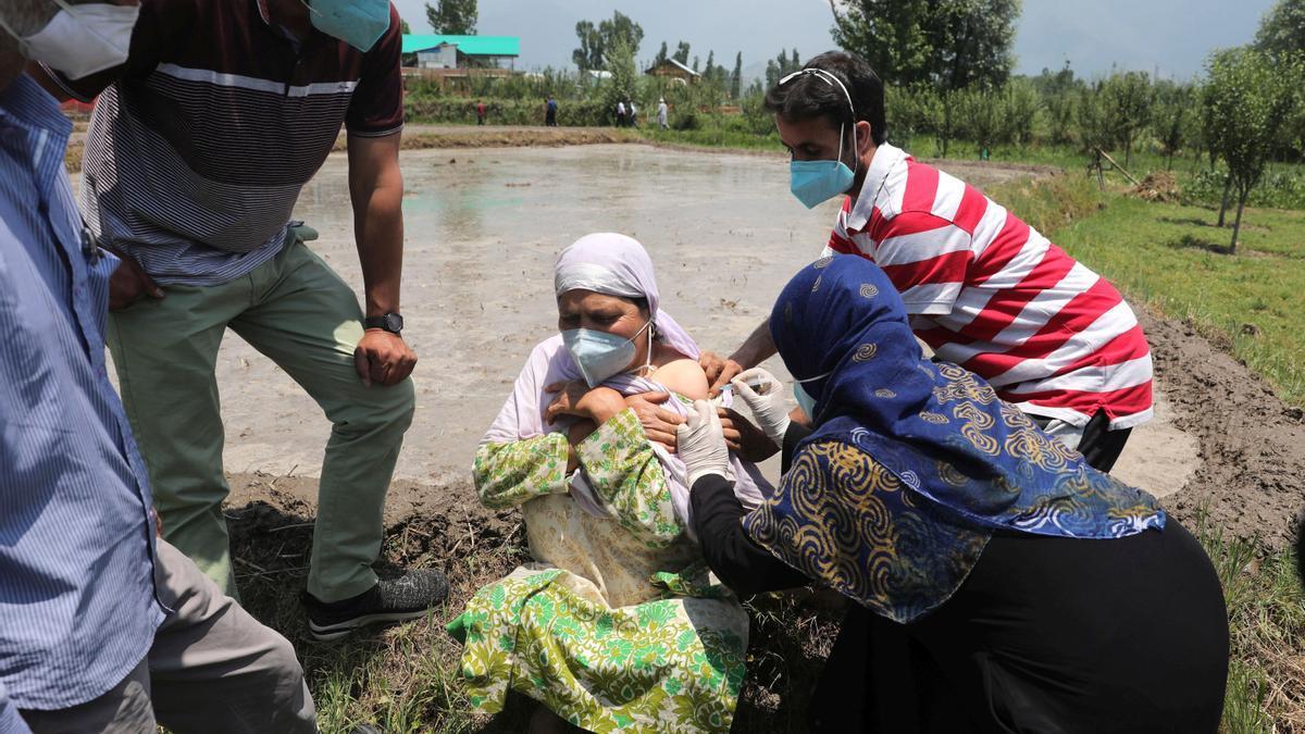 Una mujer es vacunada contra la covid-19, en un pueblo cercano a Srinagar, capital de verano de la Cachemira india. El gobierno ha comenzado la vacunación puerta por puerta de sus vecinos para tratar de detener el avance del virus.