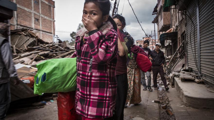Una niña se cubre la nariz debido al intenso olor a los cuerpos quemados entre los escombros de los edificios destruidos, en Bhaktapur, Nepal. / Jonathan Hyams/Save the Children.