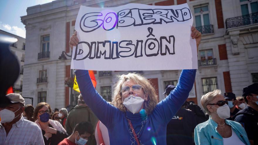 Una mujer sujeta una pancarta en la que se lee 'Gobierno Dimisión' durante una manifestación convocada por el sindicato de Vox