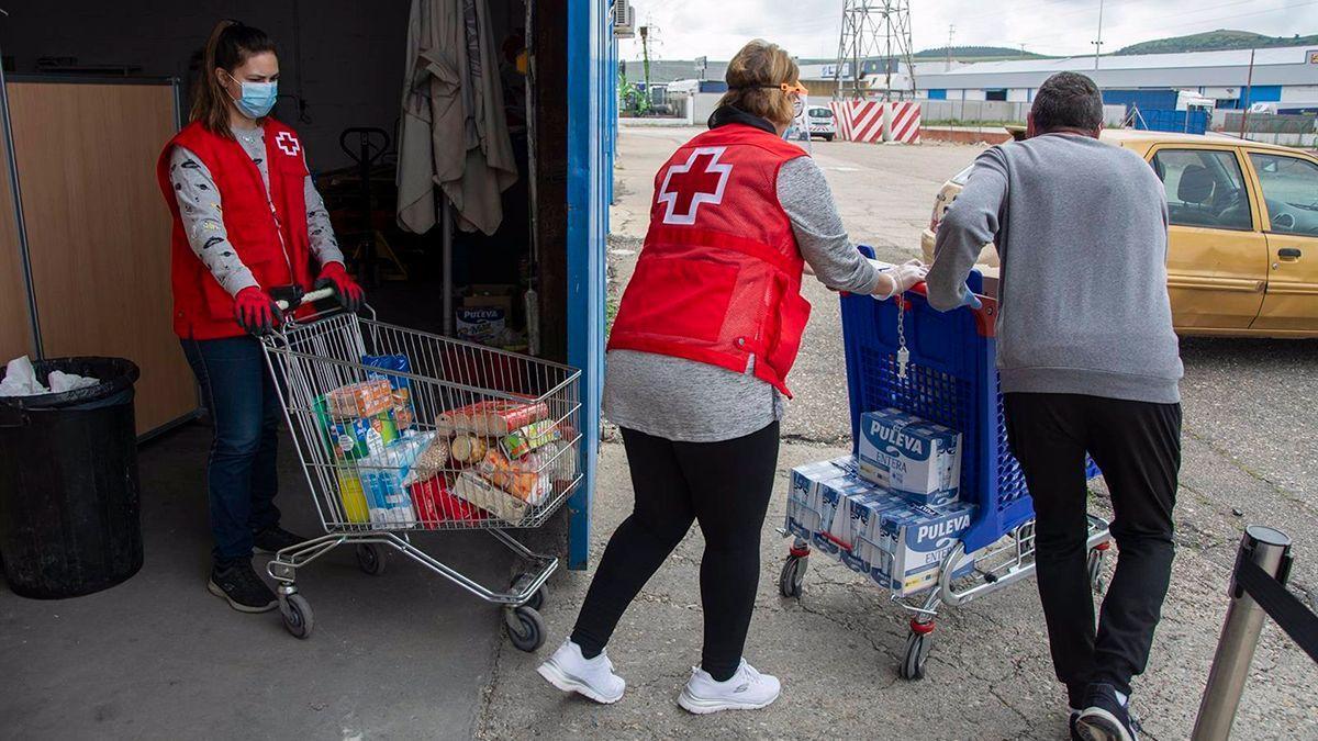 Voluntarios de Cruz Roja con carros de alimentos.