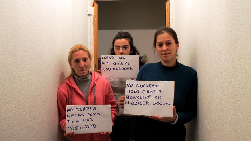 Tres de las mujeres que habitan en la Corrala de Almendralejo sostienen carteles en los que piden un alquiler social de estas viviendas abandonadas / JR