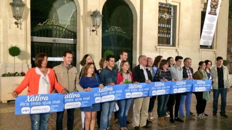 Los miembros de la lista del PP, sin Rus, posan con los xarteles electorales ante el ayuntamiento de Xàtiva