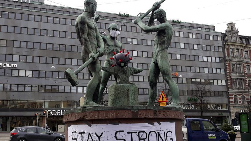 Estatua de los tres forjadores en una céntrica plaza de Helsinki (Finlandia) con mascarillas en solidaridad con los afectados por coronavirus.