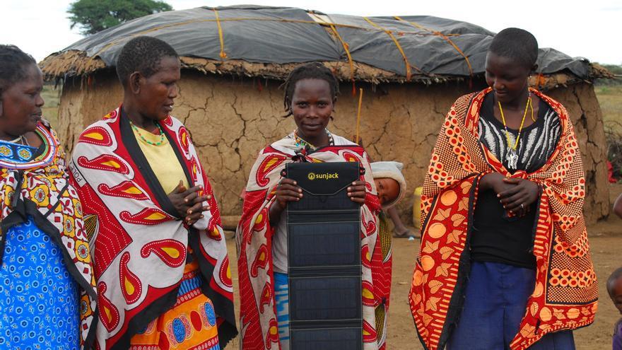 Habitantes rurales africanos sostienen placas solares // Wikimedia: SunJack