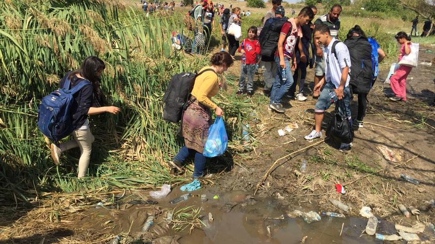 Grupo de refugiados en la frontera serbia cruzando un riachuelo entre el fango (Juan Luis Sánchez)