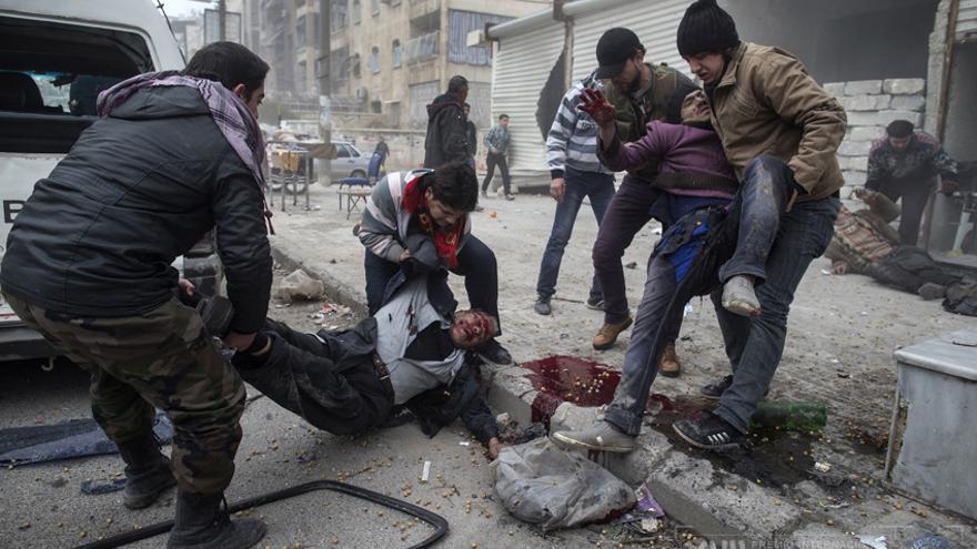 Un hombre ayuda a transportar el cadáver de un civil muerto tras un ataque con morteros en el barrio de Saif al-Dawlah de Alepo. Seis personas murieron y dieciséis resultaron heridas./ Niclas Hammarström