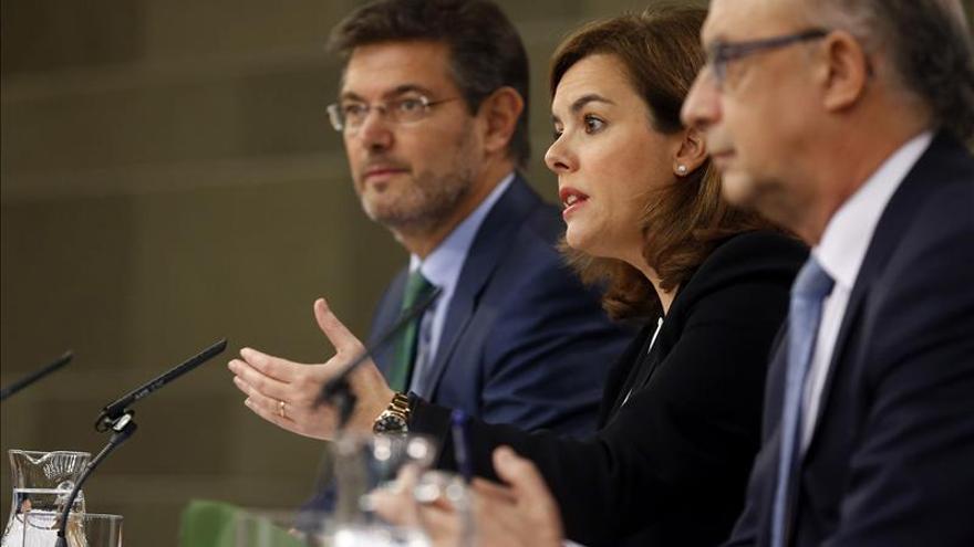 El ministro de Justicia junto a la vicepresidenta del Gobierno y el titular de Hacienda