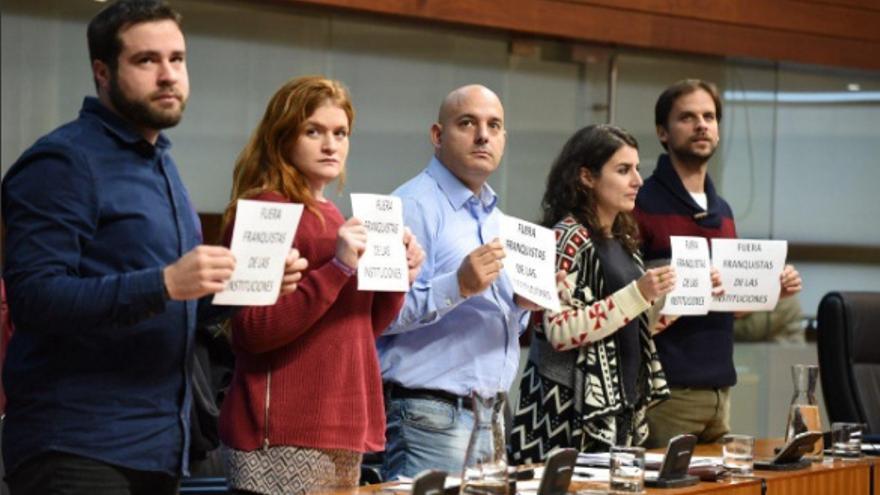 Diputados de Podemos protestan en el pleno de la Asamblea con el mensaje #FueraFranquistasDeLasInstituciones / @Podemos_EXT