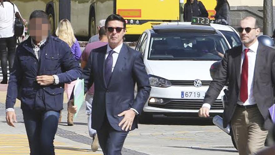 José Manuel Soria, junto a su abogado, Nicolás González-Cuéllar, y un escolta policial, en la Ciudad de la Justicia de Las Palmas de Gran Canaria. (ALEJANDRO RAMOS)
