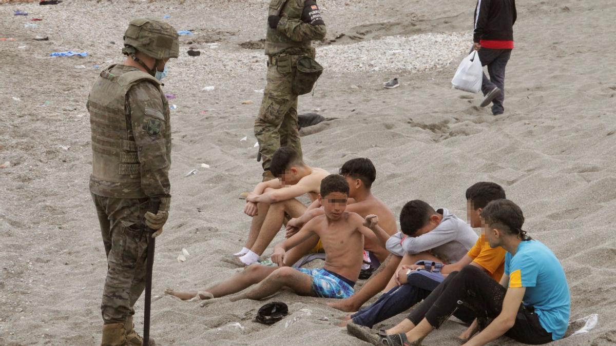 Miembros del Ejército de Tierra vigilan a un grupo de inmigrantes menores tras cruzar uno de los espigones fronterizos de Ceuta este martes