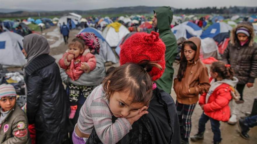Un grupo de refugiados espera para cruzar la frontera entre Grecia y Macedonia en un campamento de refugiados cerca de Idomeni (Grecia), 9 de marzo de 2016.