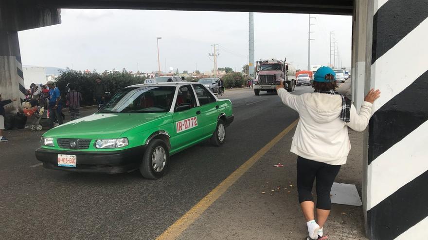 Una integrante de la caravana hace autostop para seguir su camino.