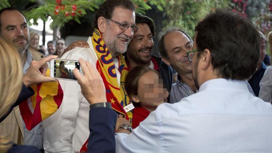 Fotografía facilitada por el PP, del presidente del Gobierno en funciones, Mariano Rajoy, que se fotografía con seguidores de la selección española, en una terraza de Tenerife, donde ha seguido el partido de la Eurocopa entre España y Turquía. EF