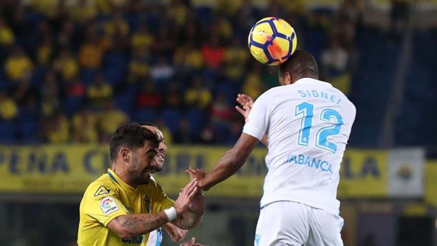 El defensa brasileño del Deportivo Sidnei (d) despeja de cabeza junto al centrocampista de la UD Las Palmas Tana (i)