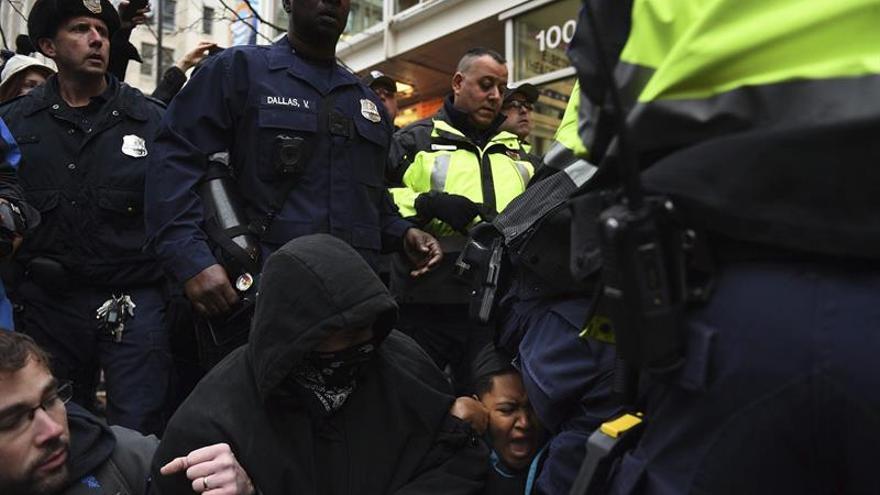 La policía trata de retener a unos manifestantes que bloqueaban una de las entradas de la ruta del desfile de inauguración, cercano a la avenida Pennsylvania, como protesta contra el presidente electo de los Estados Unidos, Donald Trump, en Washington, Estados Unidos, hoy, 20 de enero de 2017. EFE