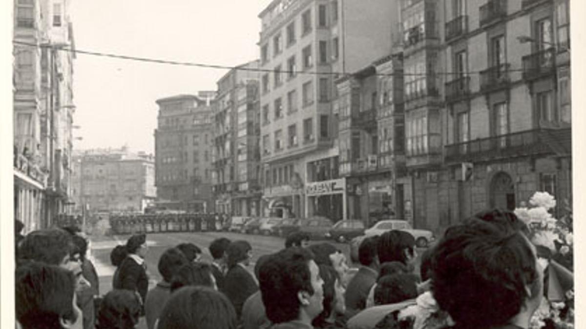 Trabajadores se reúnen en el centro de Vitoria, con la policía al fondo acordonando la zona