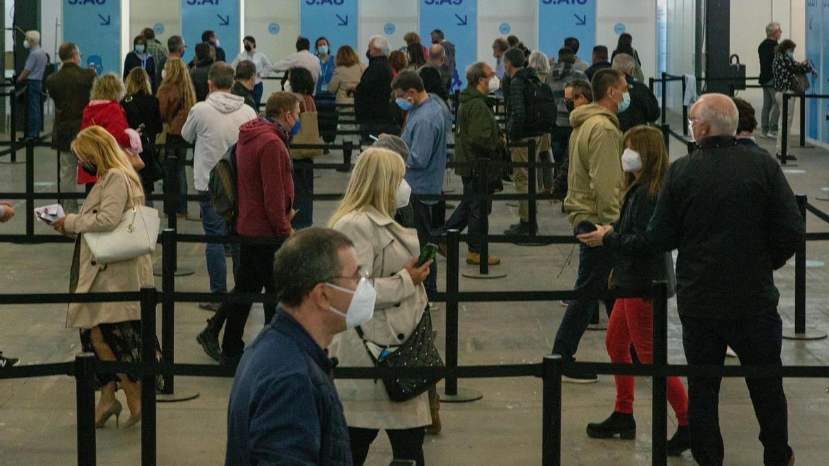 Decenas de personas entre 55 y 59 años hacen cola para vacunarse en el centro de vacunación de la Fira de Barcelona este martes.