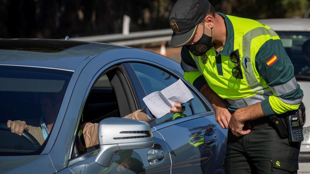 Un agente de la Guardia Civil un documento aportado por un conductor durante un control