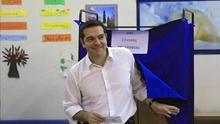 Alexis Tsipras, primer ministro griego y candidato de Syriza, sale de una cabina electoral para depositar su voto. / EFE