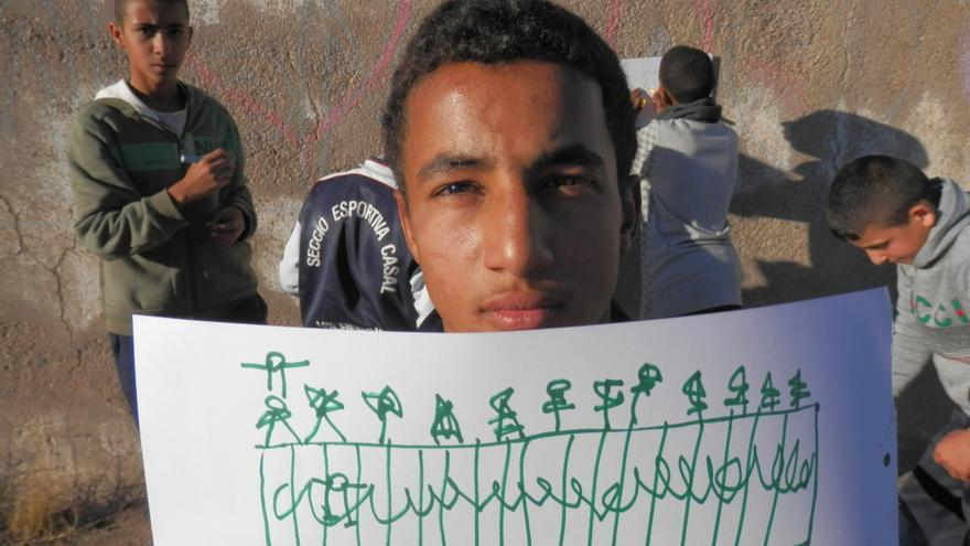 Un joven muestra un dibujo de la valla de Melilla. / FOTO: Olentzero munduan