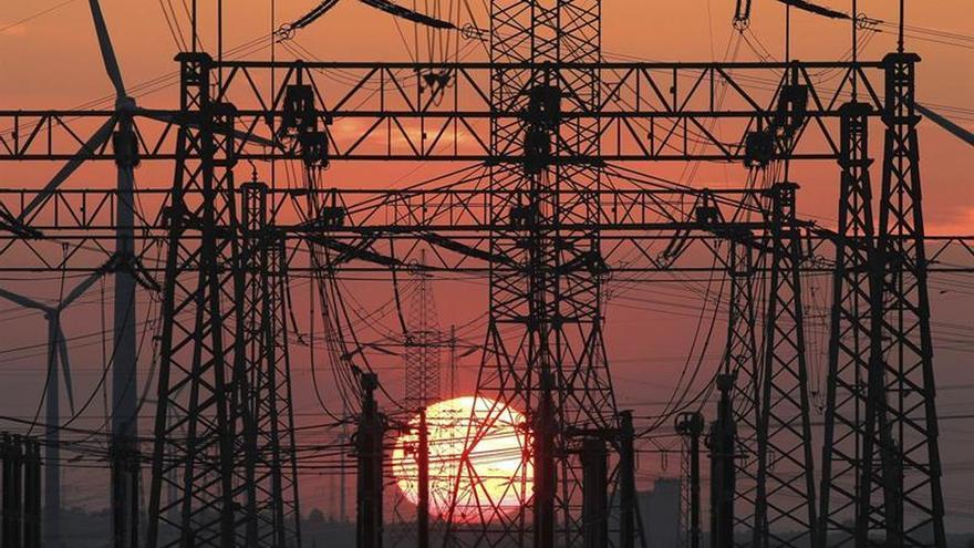 En la imagen, puesta de Sol junto al tendido eléctrico y unos molinos de viento.