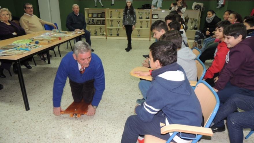 Un hombre enseña a los niños de este proyecto como se jugaba hace 50 años con un patinete artesanal.