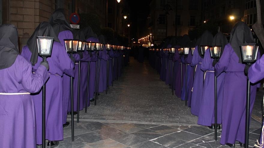 Penitentes recorriendo la procesión en su paso por la Calle San Miguel