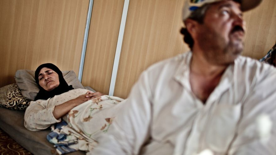Hamda Saleem, de 49 años, y su esposo en el campo de refugiados de Za'atari, Jordania. Ella permanece tumbada en la cama. Hace meses quedó atrapada en un fuego cruzado en su ciudad, Dera'a. Recibió tres balazos, dos de ellos en el pecho –una de las balas sigue alojada ahí– y otro en la espalda. Fue tras extraerle este proyectil cuando sus piernas se paralizaron para siempre. En uno de los rincones del container su silla de ruedas acumula polvo porque es infinitamente difícil hacerla rodar sobre la tierra repleta de socavones del campo./ Pablo Tosco/Oxfam Intermón