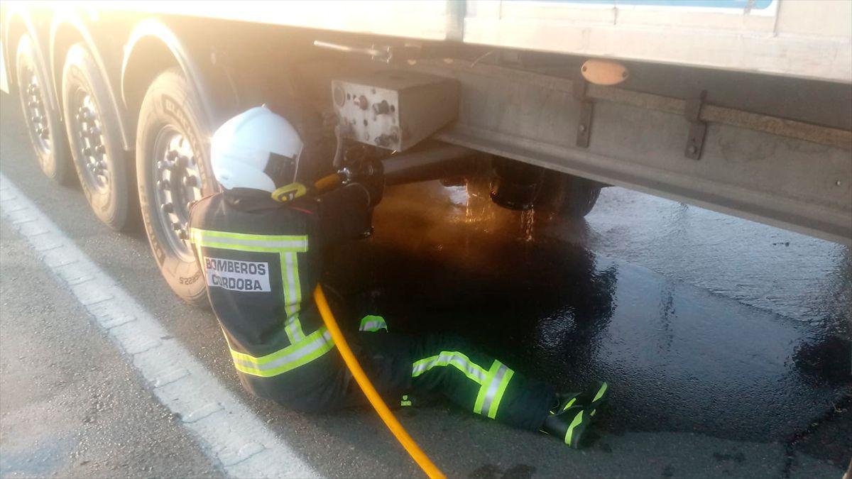 Un bombero sofoca el incendio que se iniciaba en las ruedas del tráiler en la A4.