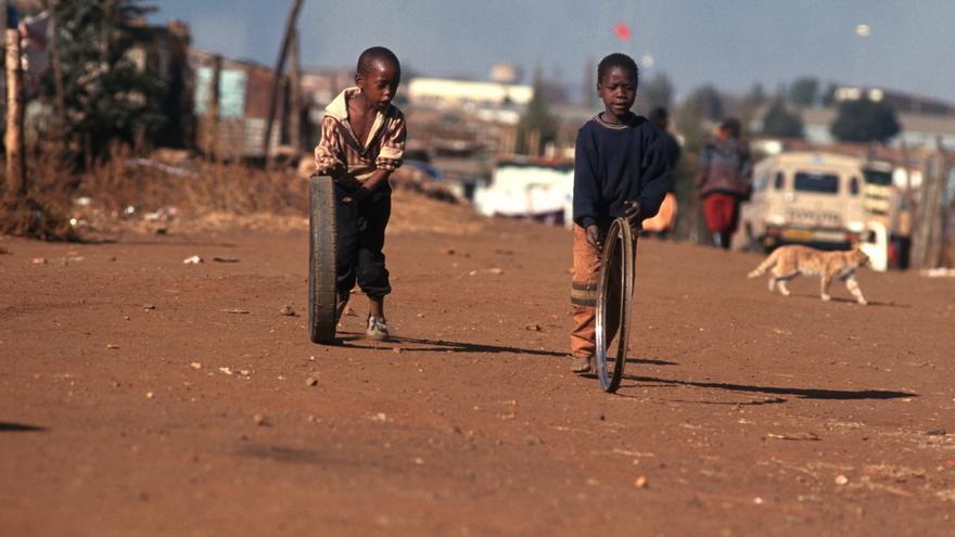 Unos niños juegan en una calle sin asfaltar del histórico gueto de Soweto, en Sudáfrica.