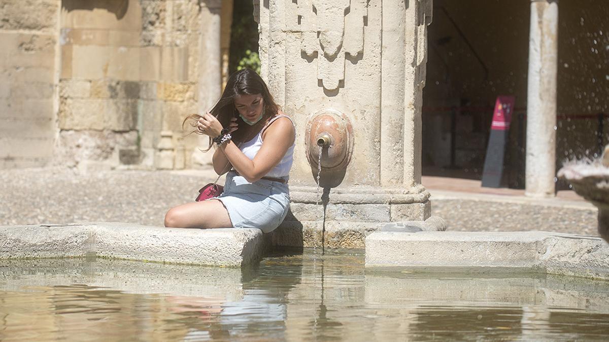 Una mujer se refresca en una de las fuentes del Patio de los Naranjos