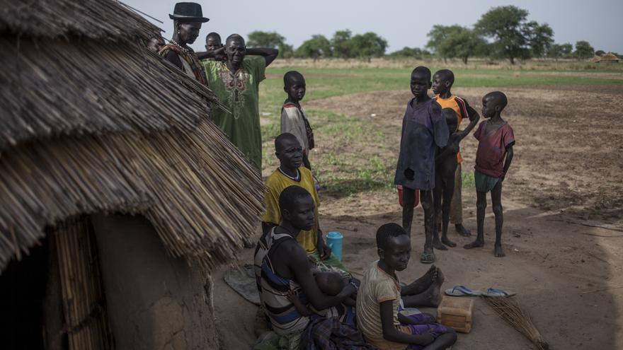 Worgok Malluac, 60, camiseta amarilla, de etnia dinka, sentada a la puerta de su casa en el pueblo de Padual, junto a su hija desplazada interna de la violencia en el condado de Pagor. Paduel, Sudán del Sur./ Fotografía: Gabriel Pecot - Oxfam Intermón